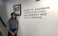Tereese Smith stands in front of the Honey W. Nashman Center logo